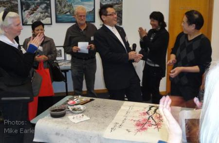 From left: Jan McLeod, Whanganui, Sook Hua Lee and Dave Bromwich, Hawke's Bay, Raymond Huo, MP, and Tibetan artist Dan Zeng applaud Jim Lin far right after his painting demonstration.