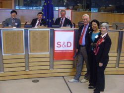 Dave and Jing at Social Democrats Europe.  Stephen Hughes is seated above the 'S&D' sign