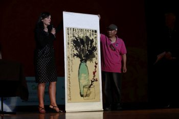 Hamilton Mayor Julie Hardacre being presented with painting painted on stage by Mr Xi Guoxing (Wuxi)
