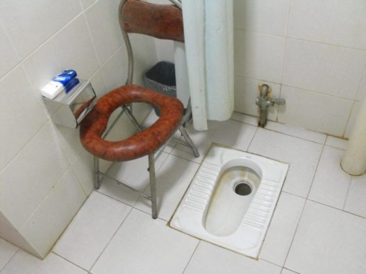Commode chair next to typical Chinese toilet,  in the 'Worker Peasant Soldier Hotel', Dayi, nr. Chengdu, Sichuan province