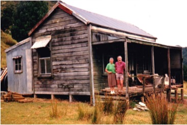 "The whare as it was in 1988 - ""Home only to pig hunters and possum trappers"".  Philippa Reynolds (Rewi's niece) is on left and Maurice Alley on right"