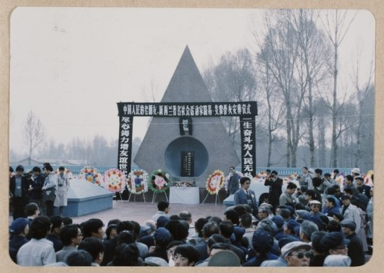 Crowd at Rewi Alley's funeral service, China. People are gathered around a dias backed by a triangular monument. On one side of the dias is the grave of English born school teacher, George Hogg with whom Rewi had worked from 1942 until Hogg's death at the age of 29 in 1945. On the right hand side of the dias is the grave of Rewi Alley. Photographed by an unknown photographer in December 1987.   Ref: PA1-f-148-449-1. Alexander Turnbull Library, Wellington, New Zealand. http://natlib.govt.nz/records/22716450