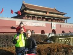 a man woman and child standing outside of a Chinese architectured building
